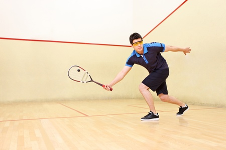 A squash player hiting a ball in a squash court Stock Photo - 9605124
