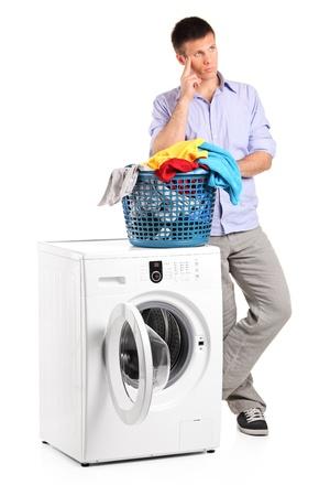 dilema: Thoughtful young man posing next to a washing mashine isolated on white background