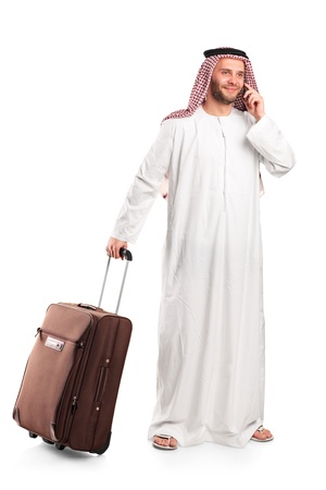 Full length portrait of an Arab tourist carrying a suitcase and talking on a mobile phone isolated on white background photo