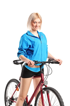 A beautiful smiling female posing next to a bicycle isolated against white background photo