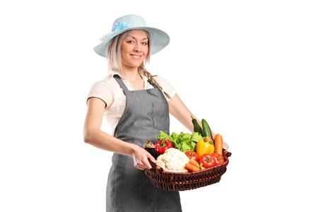 joven agricultor: Un agricultor mujer sonriente sosteniendo una cesta llena de verduras aisladas sobre fondo blanco
