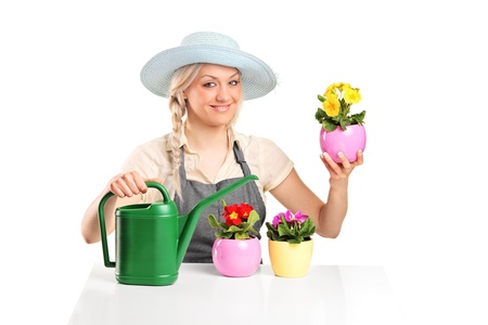 A smiling female gardener posing with flower pots and watering can isolated on white background photo