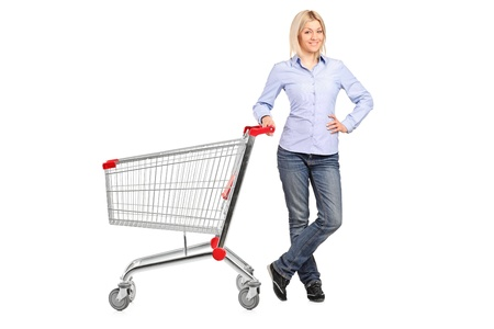 shopping cart: A smiling woman posing next to an empty shopping cart isolated on white background