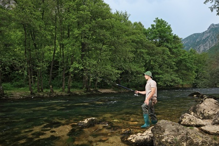 A view of a young fisherman fishing on a river with trees in the background photo