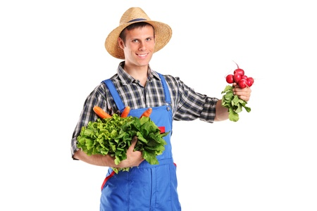 A young farmer holding vegetables isolated on white background photo