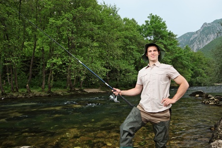 A young fisherman posing while fishing on a river with trees in the background photo