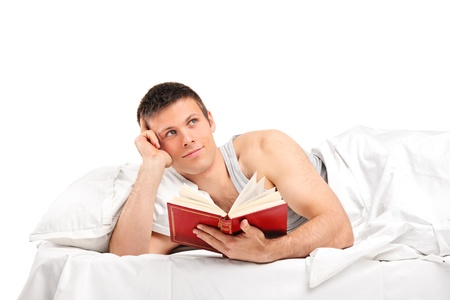 A young thoughtful man with a book lying on his bed isolated on white background photo