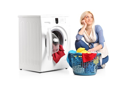thinking machines: A young woman in thoughts with clothes seated next to a washing machine isolated on white background Stock Photo