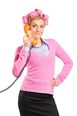 A young woman with hair rollers gossiping on a phone isolated on white background Stock Photo - 9683303