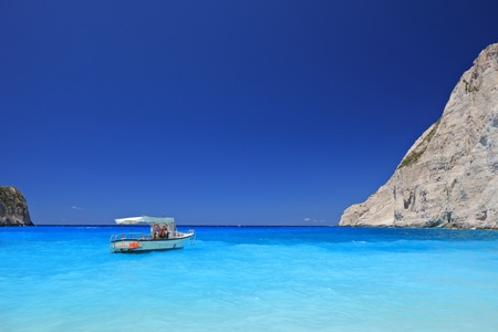Boat anchored on Navagio beach (also known as shipwreck beach), Zakynthos island, Greece photo