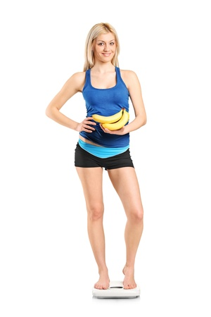 Full length portrait of a female athlete on a weight scale holding bananas isolated on white background photo