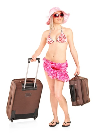 Full length portrait of a tourist girl in a swimsuit carrying a luggage isolated against white background photo