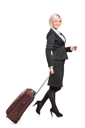 Full length portrait of a young businesswoman carrying a luggage isolated on white background photo