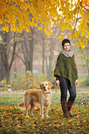 Young girl and her dog (Labrador retriever) walking in autumn in a city park Skopje, Macedonia photo