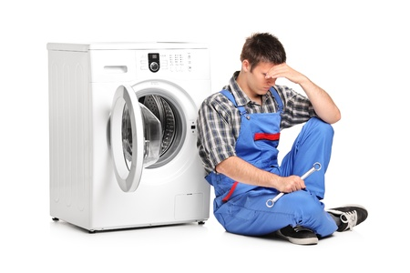 A desperate repairman posing next to a washing machine isolated on white background photo