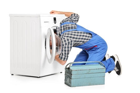 A repairman trying to fix a washing machine isolated on white background photo