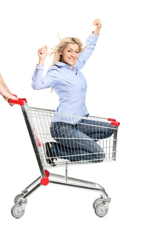 A smiling woman riding in a shopping cart isolated on white background photo