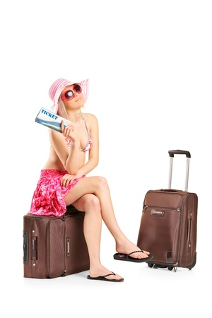 A tourist girl in a swimsuit with ticket sitting on a luggage isolated on white background photo