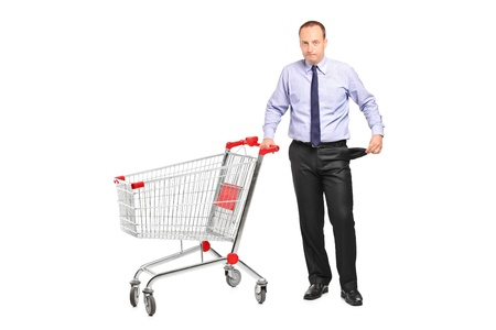 A bankrupt businessman turns out his empty pocket and an empty shopping cart isolated on white Stock Photo - 9655687
