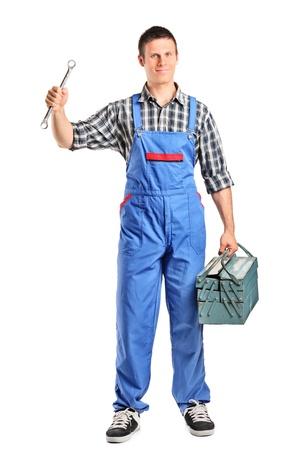 overall: Retrato de longitud completa de un reparador en general con una llave y herramientas aisladas sobre fondo blanco Foto de archivo