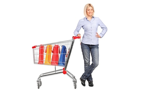 Full length portrait of a smiling female posing next to a shopping cart full with shopping bags isolated on white background Stock Photo - 9655701