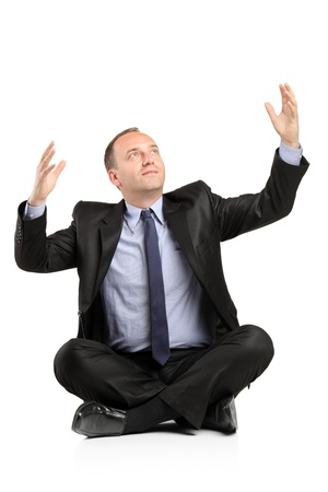 A businessman seated on a floor with raised hands isolated on white background Stock Photo - 9655707