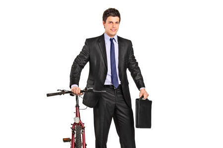 Portrait of a young businessman posing next to a bicycle isolated against white background photo