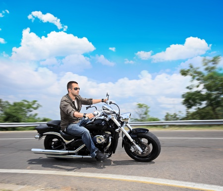 motorcycle wheel: A view of a young man riding a motorcycle on an open road Stock Photo