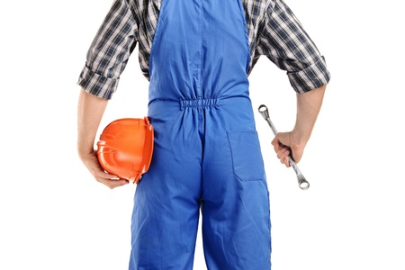 A back view of a repairman in overall holding a wrench and helmet isolated on white background photo