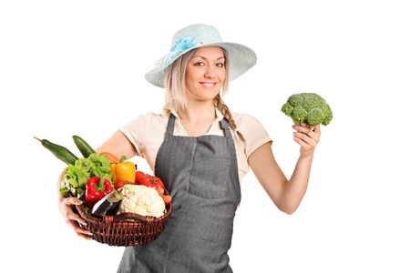 A smiling female farmer holding a various vegetables isolated on white background photo