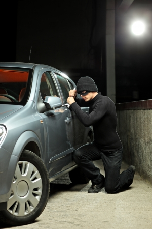 A thief wearing a robbery mask trying to steal a car photo