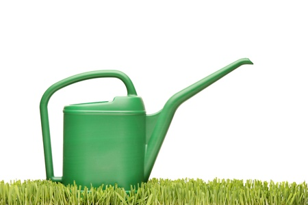 A watering can on a green grass isolated on white background photo