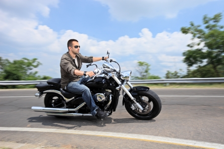 A young man riding a motorcycle photo