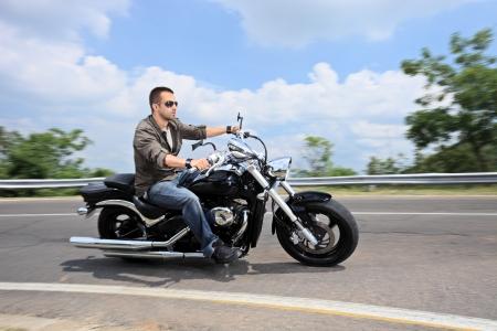 jinete: Un joven conducir una motocicleta Foto de archivo