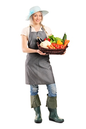 Full length portrait of a female gardener holding a basket of vegetables isolated on white background photo