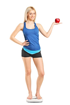 sportswoman: Full length portrait of a smiling woman holding a red apple and standing on a weight scale isolated on white background