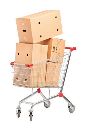 Shopping cart and stack of cardboard boxes isolated on white background photo