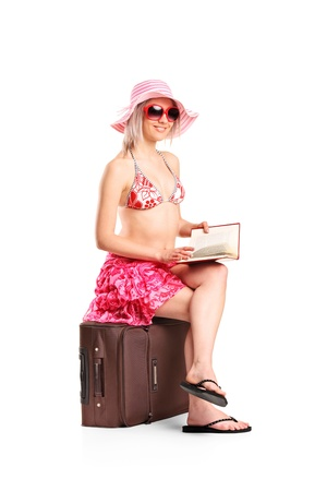 Tourist girl reading a book seated on a luggage while waiting isolated on white background photo
