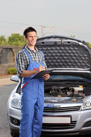 Young mechanic with a clipboard standing next to a car with open hood photo