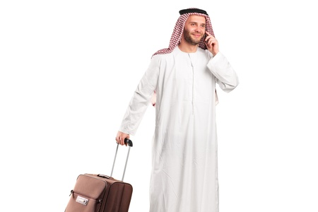 Arab tourist carrying a suitcase and talking on a mobile phone isolated on white background photo