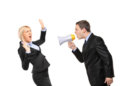 shout: Angry businessman yelling via megaphone to a businesswoman isolated on white background Stock Photo