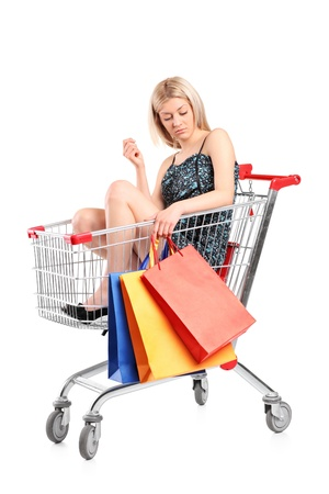 A blond woman with shopping bags posing into a shopping cart isolated on white background  photo