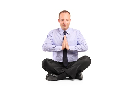 A businessman doing yoga exercise seated on a floor isolated on white background Stock Photo - 9814743