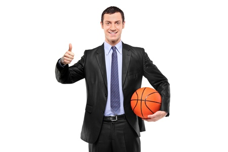A happy businessman holding a basketball and giving thumb up isolated on white background photo