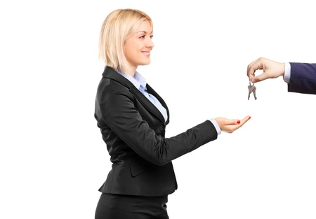 A blond businesswoman taking keys from a businessman isolated on white background Stock Photo - 9814744