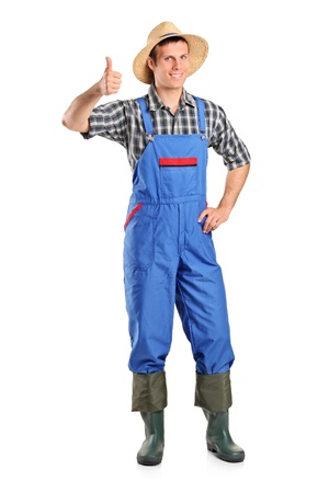 overalls: A young smiling farmer giving a thumb up isolated on white background