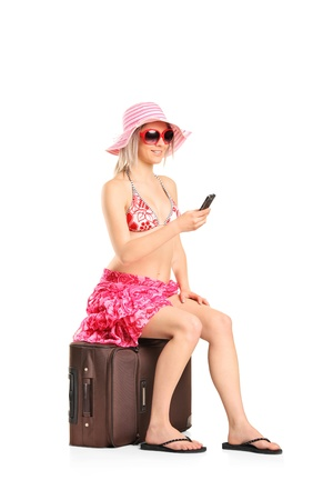 A young tourist woman typing a sms seated on a her luggage isolated on white background photo