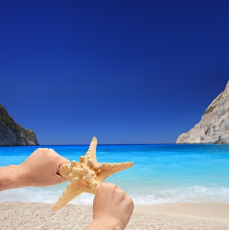 Person holding a starfish on a sandy beach on  Zakynthos island, Greece Stock Photo