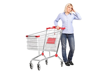 moneyless: A bankrupt woman posing next to an empty shopping cart isolated on white background
