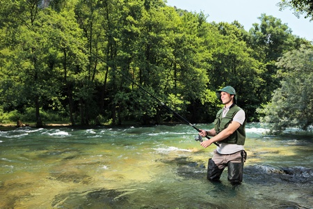 flyfishing: A fisherman fishing on a river with forest in the background